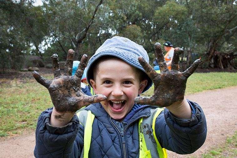 Child With Muddy Hands During Batman Park Kindergarten's Bush Kinder Programme. Photography By Birdhouse Digital.