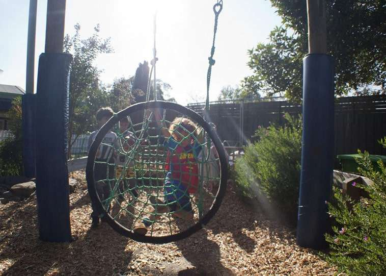 A Child Dressed As Superman On The Swing In The J.S Grey Kindergarten Outdoor Play Area.